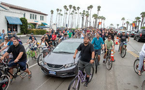 A throng of cyclists surrounds a car during the 35th annual Fiesta Cruiser Run on Sunday.