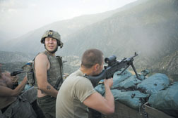 Misha Pemble is startled by the sound of gunfire during a firefight across the valley with insurgents at the Restrepo outpost in the Korengal Valley of Kunar Province, Afghanistan. Below, Pemble, left, and Murphy, right, from the Second Platoon, enjoy a joke. At bottom, clothes hang out to dry as rain clouds gather over the Restrepo bunker.