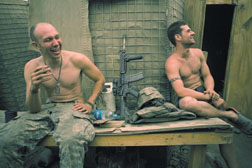 Misha Pemble (left) and Murphy (right) from Second Platoon enjoy a joke at the Restrepo outpost. Korengal Valley, Kunar Province, Afghanistan. June 2008.