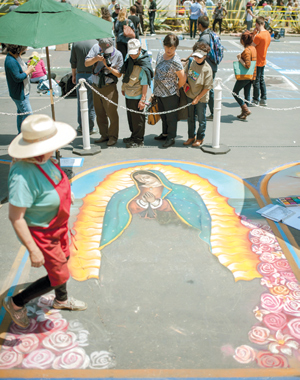 Featured artist Blair Looker's creation is appreciated by viewers at the street painting festival. Ms. Looker's work will feature Saint Barbara, Father Junipero Serra and the Virgin of Guadalupe.