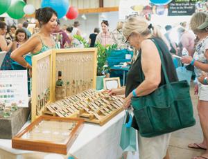 Lisa Karey of M&L Coastal Creations helps a customer shop during Saturday's Sea Glass Festival in Carpinteria. KENNTH SONG/NEWS-PRESS